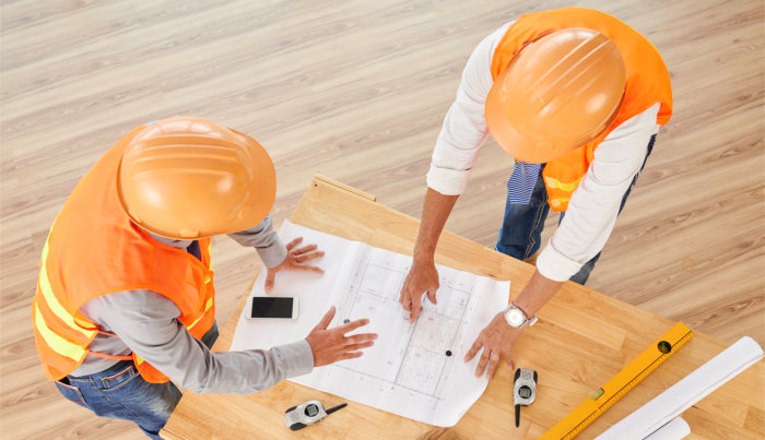 Engineers in hard hats discussing blueprint of the building on table, view from above