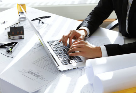 Hands of CEO of construction company in black suit typing message via e-mail to partners on laptop with drawings, seal stamp, divider on table. Young architect using netbook sitting in his office